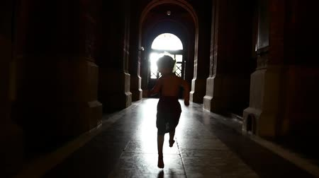 szandál : A little girl in a dress is running along the dark corridor among the columns. Playing catch-up Stock mozgókép