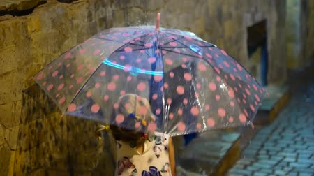 gumboots : A cute little girl is sitting by the puddle. Drops of rain flow down a multi-colored umbrella. The child smiles and enjoys the fun, slow motion Stock Footage