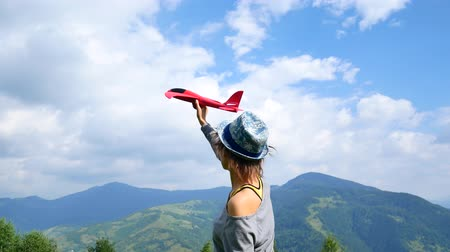 no hands : Young pretty woman back to the camera and keeps the red model of the plane in ruach. concept of travel and freedom Stock Footage