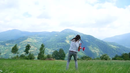 raszta : A young man with dreadlocks playing with a model airplane in the mountains.
