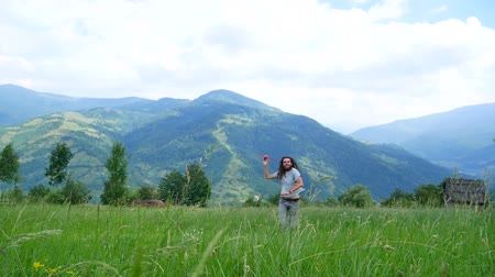 background young : A young man with dreadlocks playing with a model airplane in the mountains.