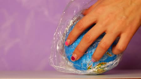 meada : Globe wrapped in plastic wrap. Waste management concept.