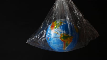 rekesz : Globe wrapped in polyethylene. dark background, space.. Symbolizes delivering packages, transportation, shipping and e-commerce.