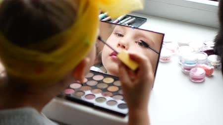 corar : A beautiful little girl at the mirror makes herself a make-up.