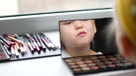 first person : A beautiful little girl at the mirror makes herself a make-up.