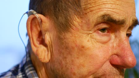 listens : old man using hearing aids.