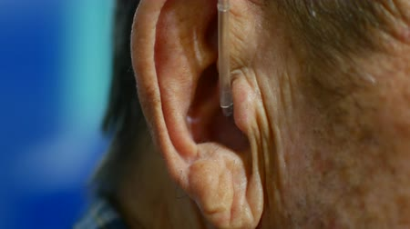 aids : old man using hearing aids.