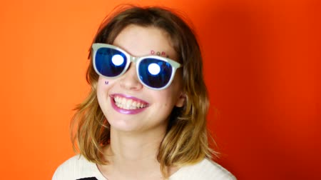 dope : Bored girl with sunglasses in hands on vivid orange background in studio. Young arrogant teenager. Stock Footage