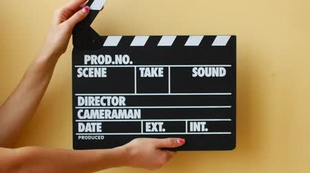 slapping : Hands using a film clapper board, close up.