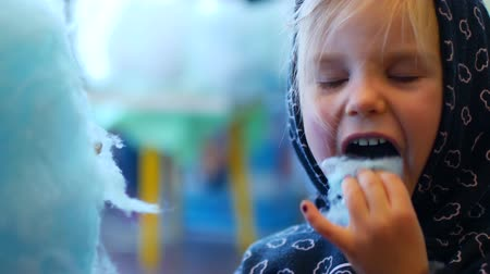 blue braid : Little girl in the hood eats blue cotton candy in the circus.