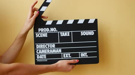 film slate : Hands using a film clapper board, close up.