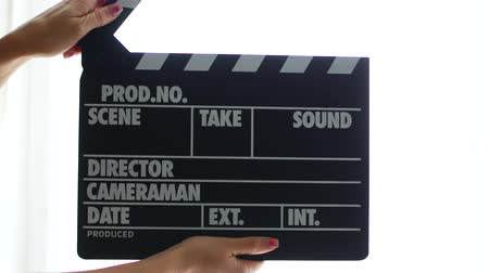 arduvaz : Hands using a film clapper board, close up.