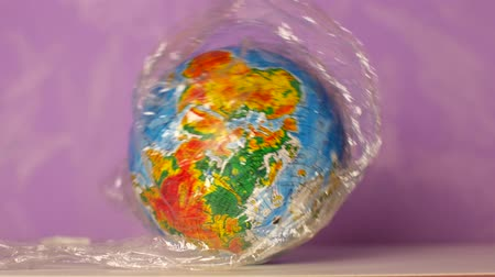 emaranhado : Globe wrapped in plastic wrap. Waste management concept.