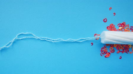 bleeding : Tampon on a blue background. Menstruation concept Stock Footage