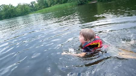 preserver : the boy floats in the river, the life jacket in action.