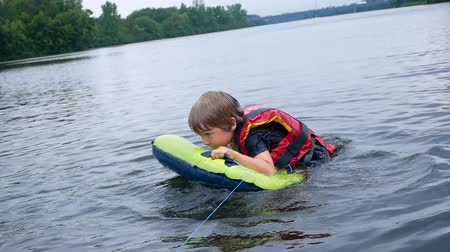 salva vidas : the boy floats in the river, the life jacket in action.