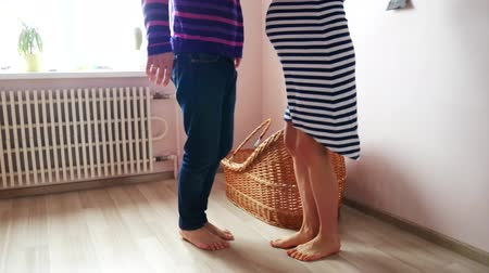 proutěný : A man and a pregnant woman are dancing near the crib. Waiting, pregnancy, family