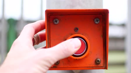 emergency stop : Hand presses the red button. Starting a mechanism or process.