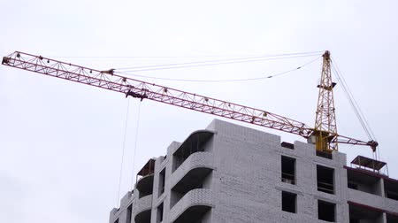 строительные леса : Construction of a multistory, brick building. A mounting crane lifts building materials Стоковые видеозаписи