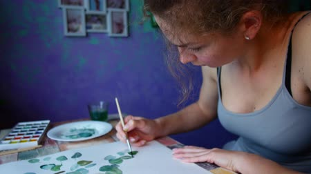 мольберт : The artist paints on paper at home.