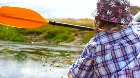 rowboat : A child paddles on a kayak paddle. Active family vacation