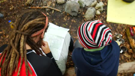 направления : Tourists are looking at a map at a campsite in the forest