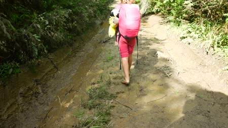 andar : Barefoot girl walks through the mud.