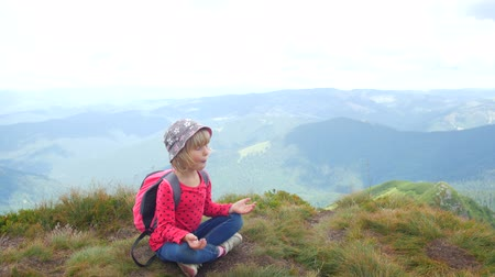 meditál : A child meditates in a lotus position on top of a mountain Stock mozgókép