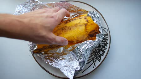 gyro : Shawarma kebab in foil, unpacking and serving on a plate.
