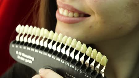 Close-up. Patient and tooth color chart. Young woman smiling. Effective teeth whitening.