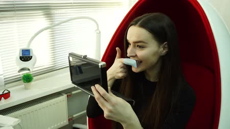 Young woman client sitting in red chair brushes tooth using nylon fabric dressed on her index finger for deep cleaning teeth