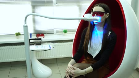 Shot of teeth whitening procedure. Powerful light source is directed at patients mouth to speed up the process.