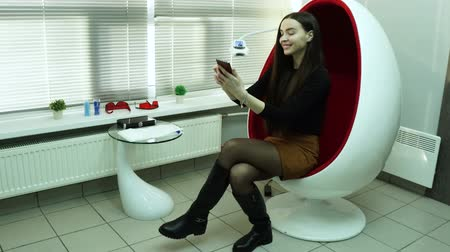 A young woman sits in a red chair and takes a selfie. Stok Video