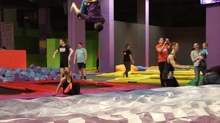 hildren and young people jumping on trampoline, sport activities for kids and elders, having fun on trampoline at local amusement park. Slow-motion.