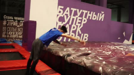 Trampoline die acrobatische stunts en tricks spint en springt. Slow-motion. Stockvideo