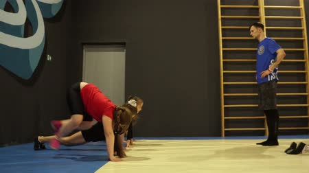 The trainer is engaged in gymnastics with children.