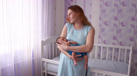 A young mother rocking a newborn in her arms. Stok Video