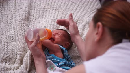 bottle feeding : A young mother feeds a newborn from a bottle.