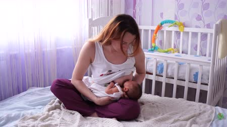 szoptatás : Young mother breast feeding newborn. Mother breastfeeding her little baby with silicone nipple. The young mother feeds the newborn breast sitting on the bed in a Lotus pose.