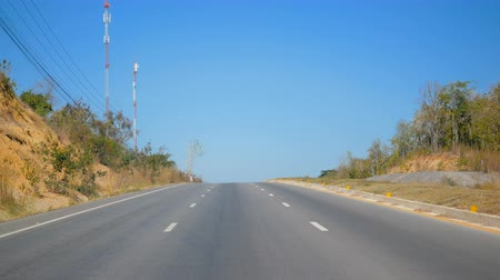 there : On the road beside there are forests and clear skies Stock Footage