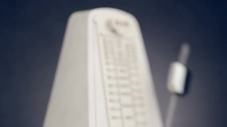 temp : Music metronome out of focus with moving pendulum in focus, ambient sound, HD 1080p, loop Stock Footage