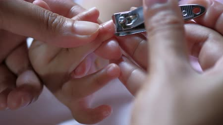 Cut fingernails. Cutting nails to a newborn baby a little mother care.