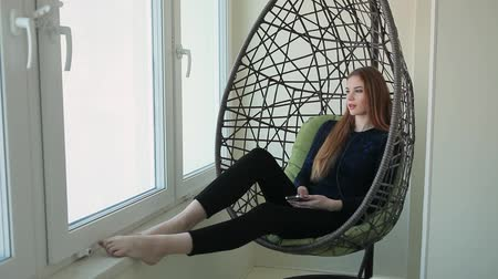 zámotek : Beautiful young woman sits in a pendant chair with the phone and listens to music