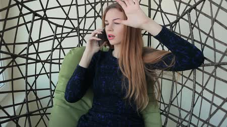 Beautiful young woman sits in a chair and talking on the phone