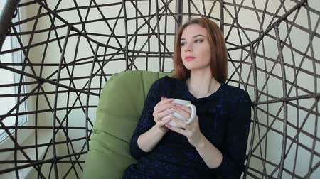Beautiful young woman sits in a pendant chair with the cup of hot tea or coffee Stock Footage