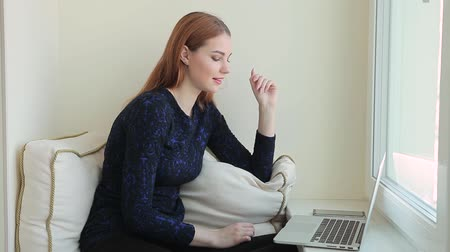 Beautiful young woman communicates in social networks in a laptop while sits at windowsill at home Stock Footage