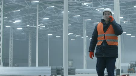 telekomünikasyon : engineer talking on the phone in new modern industry warehouse Stok Video