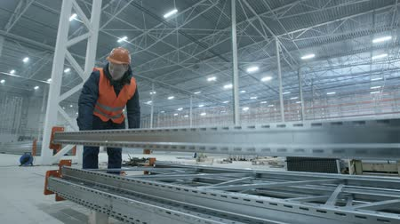 dach : man carries metal construction in new modern industry warehouse