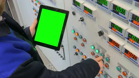 elektrownia : Engineer stands at the front of the control panel and holding a tablet with green screen Wideo