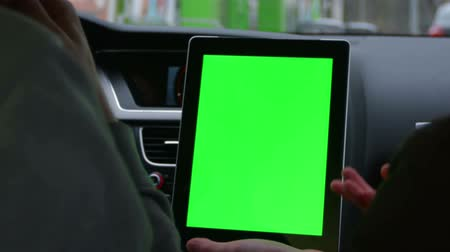přístrojová deska : two people riding in the modern car and discuss the route in tablet with green screen